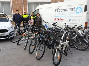 Representant de Càritas i de la Policial Local amb les bicicletes cedides