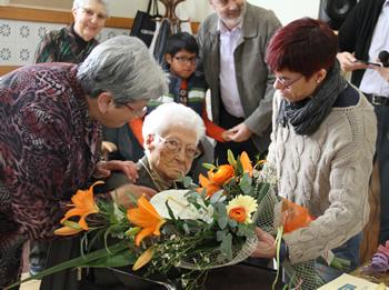 La regidora li lliura el ram de flors a l'àvia centenària