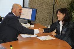La regidora Ariadna Llorens i el director de l'oficina de la Caixa, Xavier Ventosa, formalitzant la col·laboració