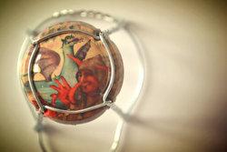 La placa de cava amb el quadre del Drac es pot adquirir a les botigues dels museus