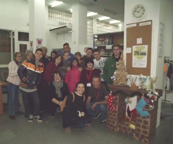 Alumnes i voluntaris al costat de la decoració nadalenca
