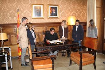 El Delegat, signant en el llibre d'honor